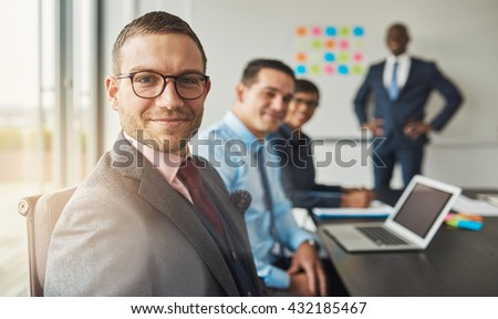 Handsome bearded man wearing suit and tie with three professional co-workers in meeting at conference table in front of a large white board - stock photo