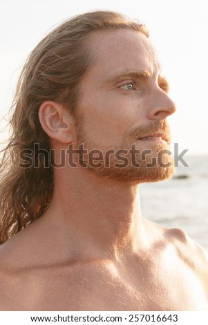 Handsome bearded man with shoulder length hair standing and at the beach staring into the summer sunshine with an intense serious expression and frown - stock photo