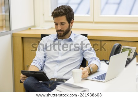Handsome bearded man working in office on computer - stock photo