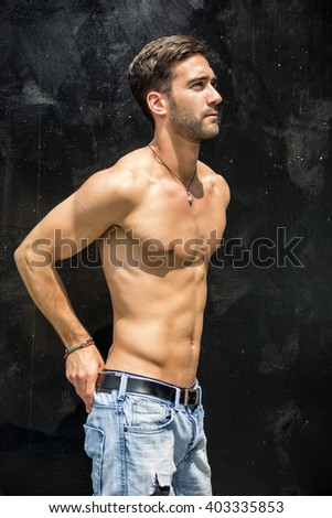 Handsome bearded shirtless young man standing against black wall - stock photo