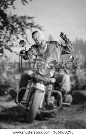 Handsome biker with beard driving his cruiser motorcycle in the forest and giving the devil horns gesture and smiling. Man is wearing leather jacket and jeans. Tilt lens blur effect. Black and white - stock photo