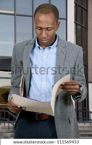 Handsome black African American business man with manila folders full of documents - stock photo