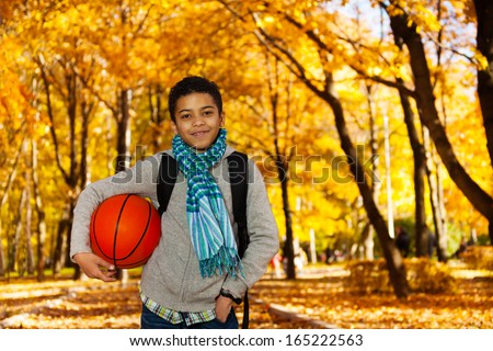Handsome black boy 10 years old standing in the autumn park under maple trees with orange basketball ball wearing casual clothes with scarf and sweatshirt - stock photo