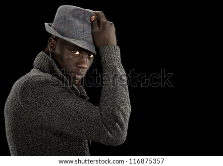 Handsome black man in a nice sweater and fedora hat looks to the camera as he raises his hat off his head. - stock photo