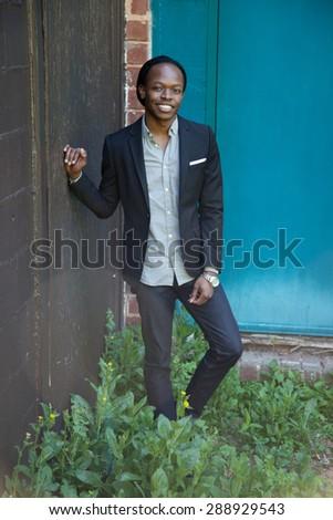 Handsome black man in suit coat, smiling - stock photo
