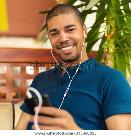 Handsome black man sitting at cafe bar, holding mobile phone and smiling.  He is listening music and looking at camera.  - stock photo