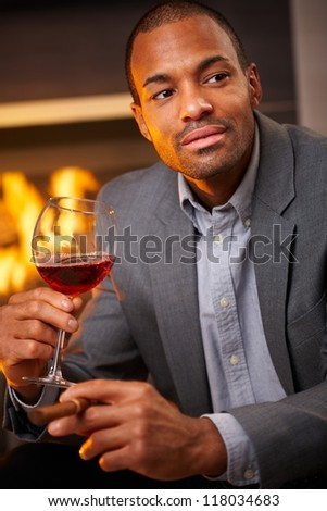 Handsome black man sitting by fireplace smoking cigar, drinking wine. - stock photo