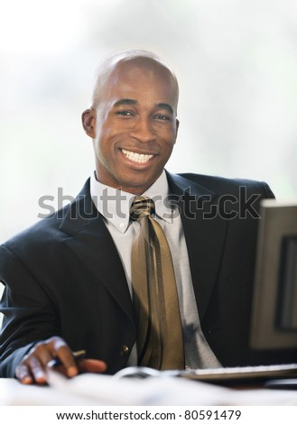 Handsome Black man wearing business attire in the office. - stock photo