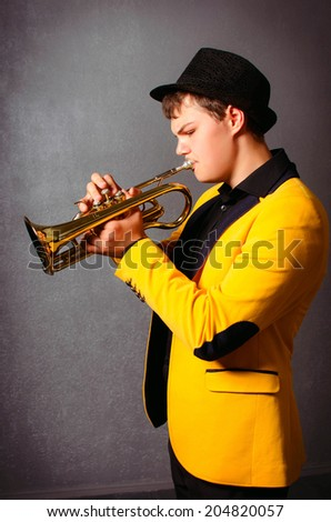 Handsome blind trumpet player in hat and yellow jacket playing trumpet. Portrait of young musician playing the trumpet at studio. - stock photo