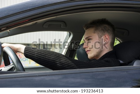 Handsome blond young man sitting in his car, looking in front of him  - stock photo