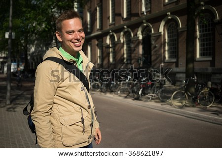 Handsome blond young man with green eyes smiling Travelling in Europe - stock photo