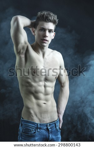 Handsome bodybuilder in relaxed pose, looking at camera on dark background - stock photo