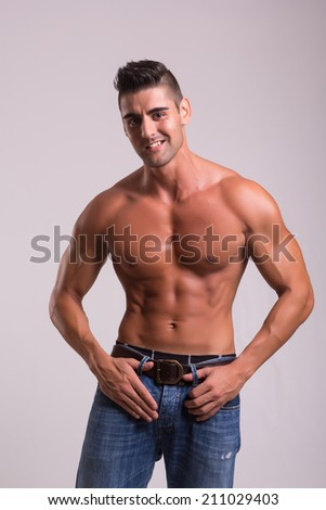 Handsome bodybuilder with a great body posing over a copy space background - stock photo