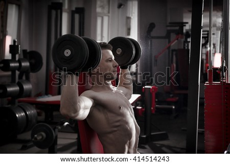 Handsome bodybuilder with muscular torso workout with dumbbells on athletic bench in gym. Perfect muscular male body. Toning image - stock photo