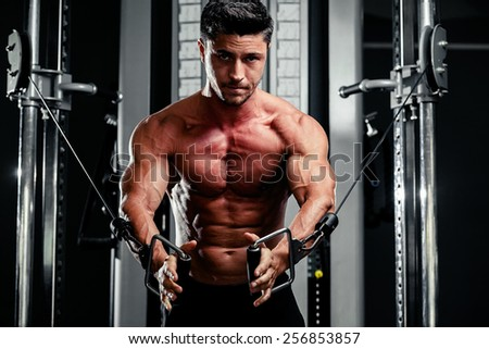 handsome bodybuilder works out  pushing up excercise in gym - stock photo