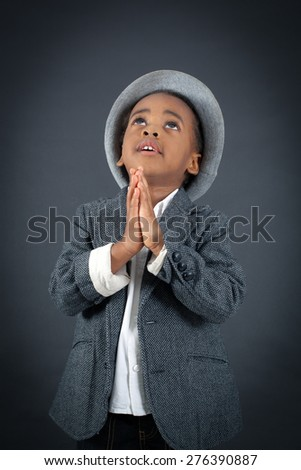 Handsome boy doing different expressions in different sets of clothes: prayer - stock photo