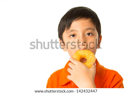 Handsome boy eating a donut. - stock photo