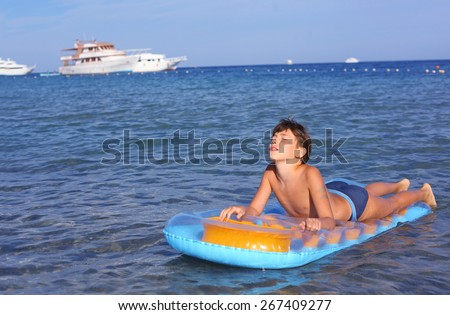handsome boy in swimming suit with inflatable matrass on the blue sea with yacht background - stock photo
