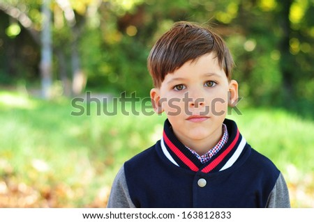 Handsome boy in the Autumn park - stock photo