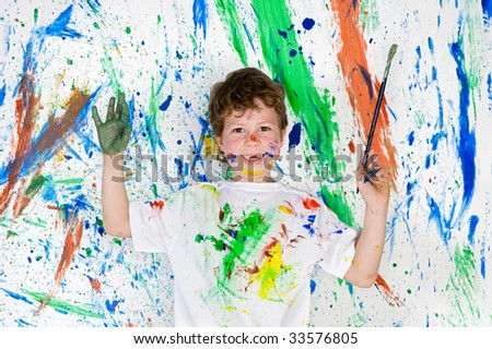 Handsome boy playing with painting with the background painted - stock photo