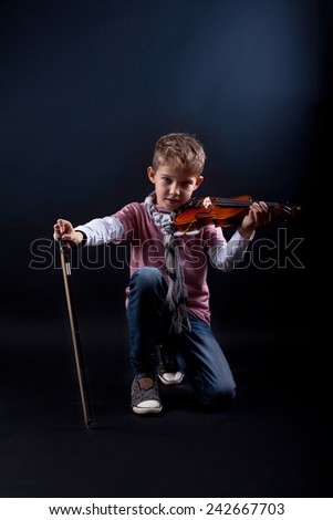 handsome boy proudly showing his fiddle - stock photo