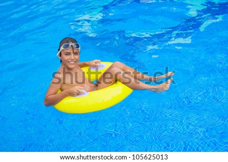 handsome  boy taking sunbath in pool on rubber ring - stock photo