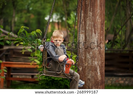 handsome boy with a sad face sited on the bench in the  summer day in park - stock photo