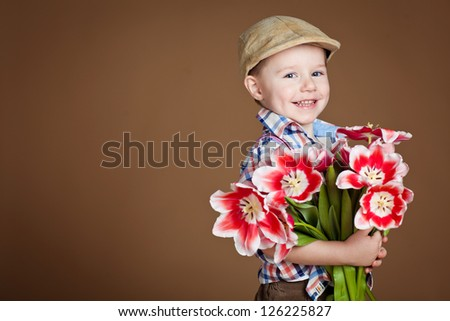 handsome boy with flowers in hands - stock photo