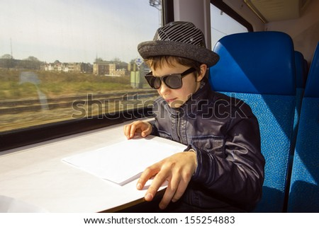 Handsome boy with sunglasses rides on a train reading from the paper - stock photo