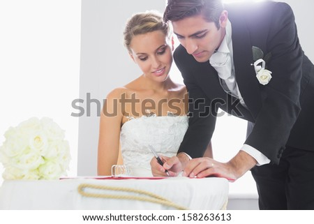 Handsome bridegroom signing wedding contract at desk - stock photo