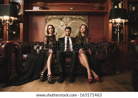 Handsome brunette wearing suit sitting on sofa with two beautiful women  - stock photo