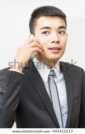 Handsome business asian man in black suit speaking on the phone on white background - stock photo