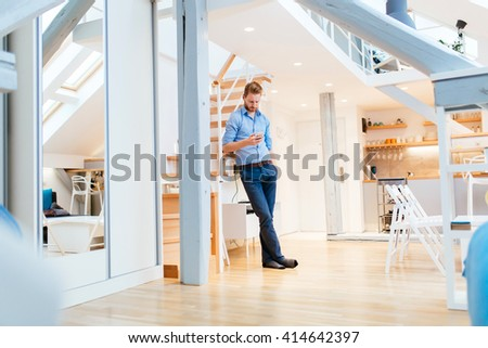 Handsome business at home holding phone and calling colleague after work - stock photo