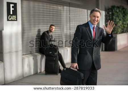 Handsome business CEO traveling alone quickly exits the airport  - stock photo