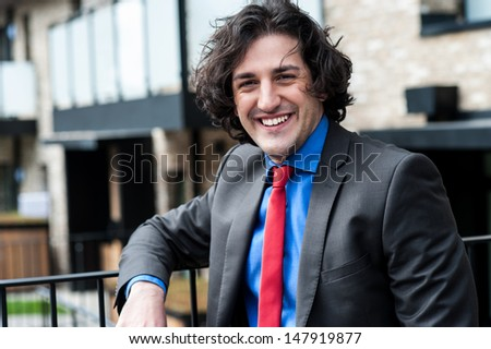 Handsome business executive posing casually, outdoors - stock photo