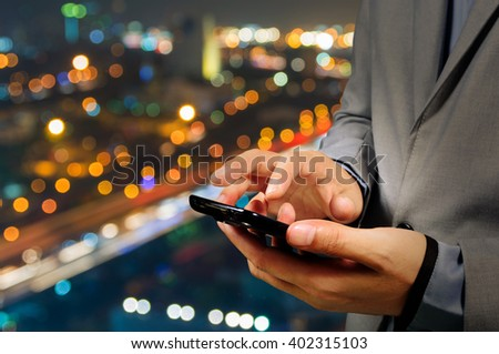 Handsome Business male in the city using his smartphone with Bokeh Background - stock photo