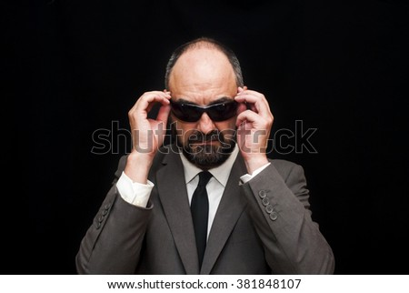Handsome business man, bald and beard, over black background - stock photo