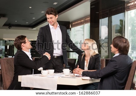 Handsome business man greeting group of people. Sitting at restaurant drinking coffee  - stock photo