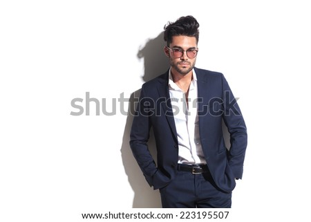 Handsome business man holding his hands in pocket while leaning on a white wall, looking at teh camera - stock photo
