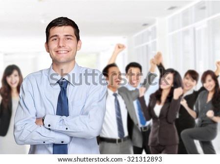 handsome business man in front of his team member celebrating their achievement - stock photo