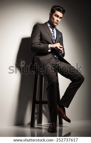 Handsome business man looking away from the camera while sitting on a stool, holding his hands together. - stock photo