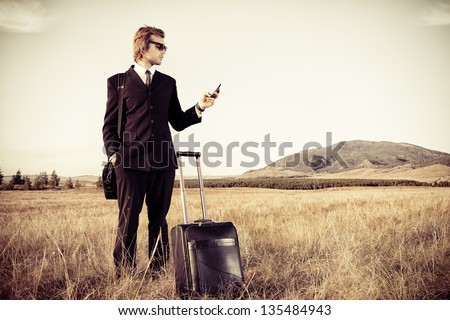 Handsome business man standing in a field with his suitcase and cell phone. - stock photo