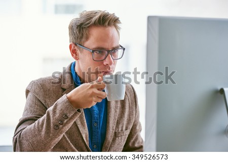 Handsome businessman about to take a sip of fresh coffee while sitting at his desk and looking seriously at his computer screen - stock photo