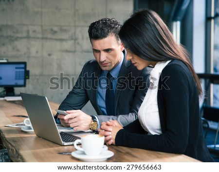 Handsome businessman and beautiful businesswoman using laptop together in cafe - stock photo
