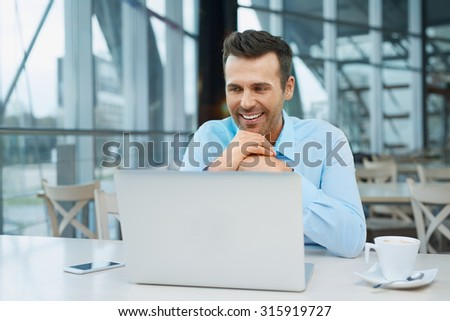 Handsome businessman at modern office working with laptop - stock photo