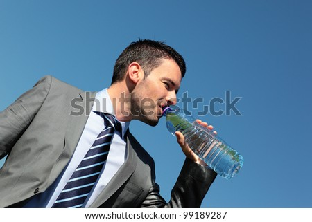 handsome businessman drinking water with bottle in summer - stock photo