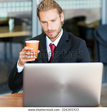 Handsome businessman enjoying a cup of coffee and using his laptop - stock photo