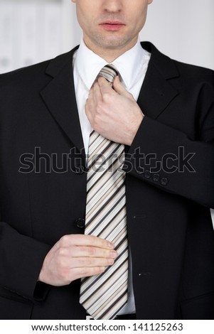 Handsome businessman fixing his tie in a close up shot - stock photo