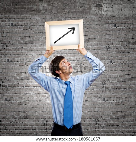 Handsome businessman holding frame with graph drawing - stock photo