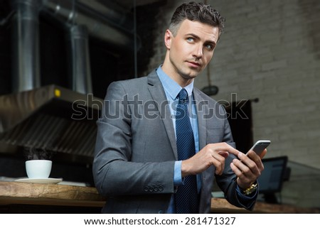 Handsome businessman holding smartphone and looking aside in cafe - stock photo